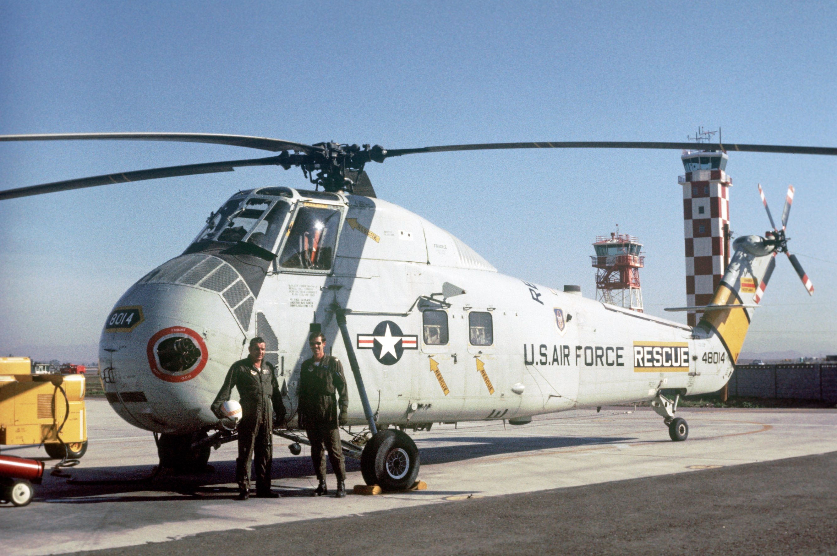 Two men standing in front of a HH-3E Jolly Green Giant helicopter