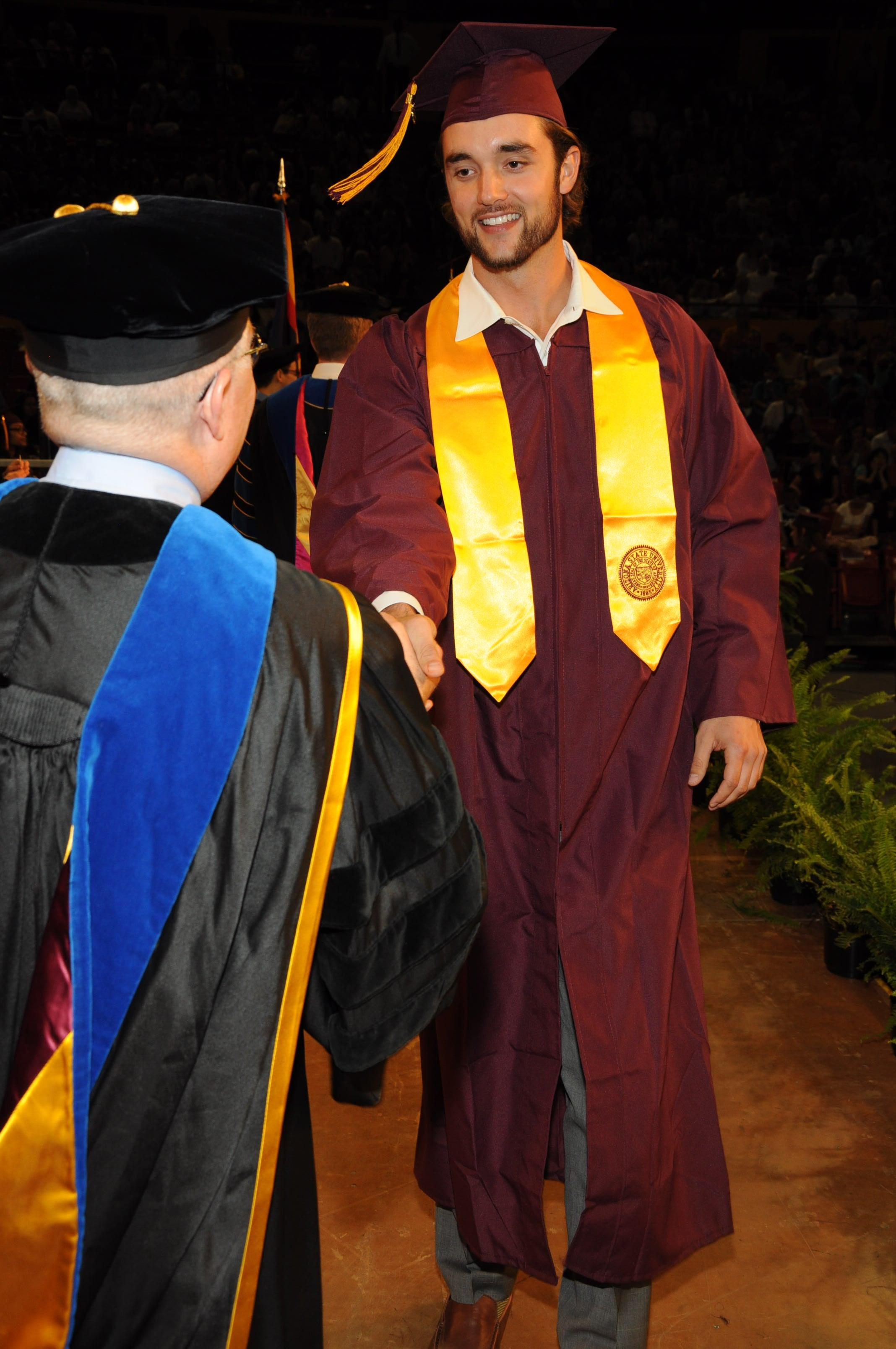 ASU College of Integrative Sciences and Arts alum and NFL QB Brock Osweiler accepts his diploma in Dec 2014 from Dean Duane Roen