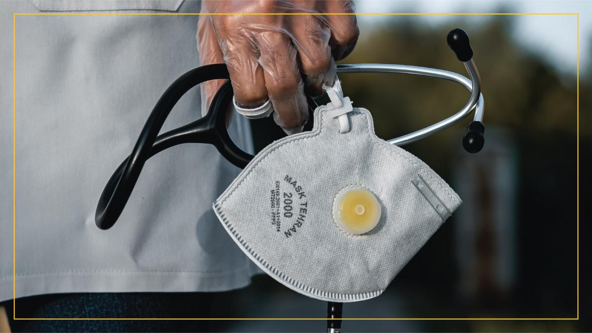 Healthcare worker gloved hand dropped at side, holding medical equipment