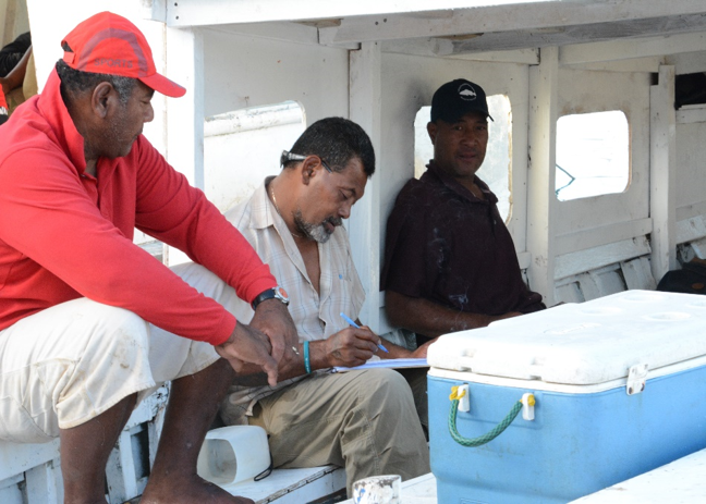 Commercial fishers on boat study data on laptop