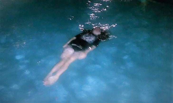 child floating on back just under surface of water