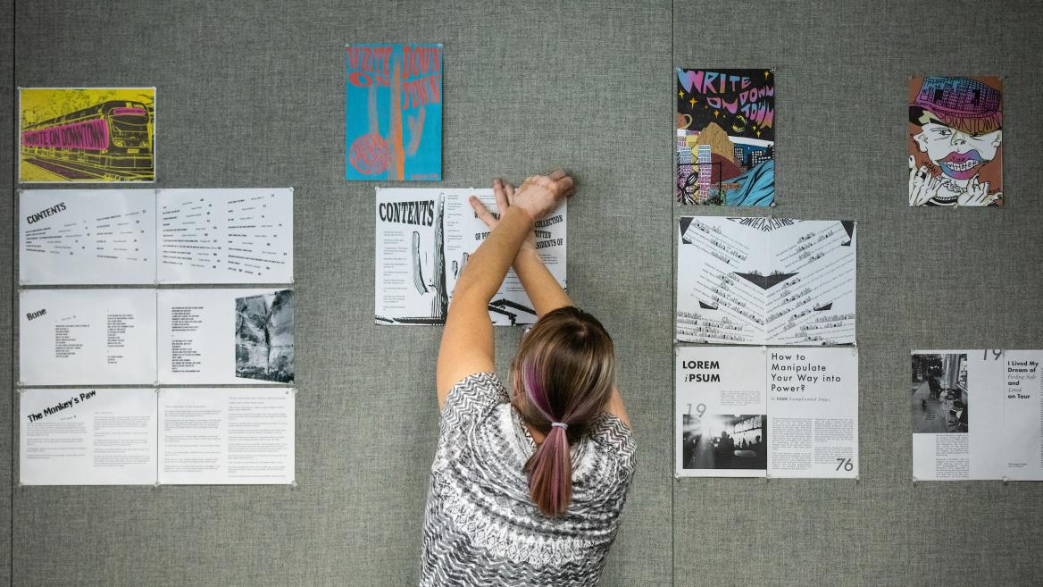 shot of a woman from the back, pinning an illustration to a wall with many illustrations already pinned on it