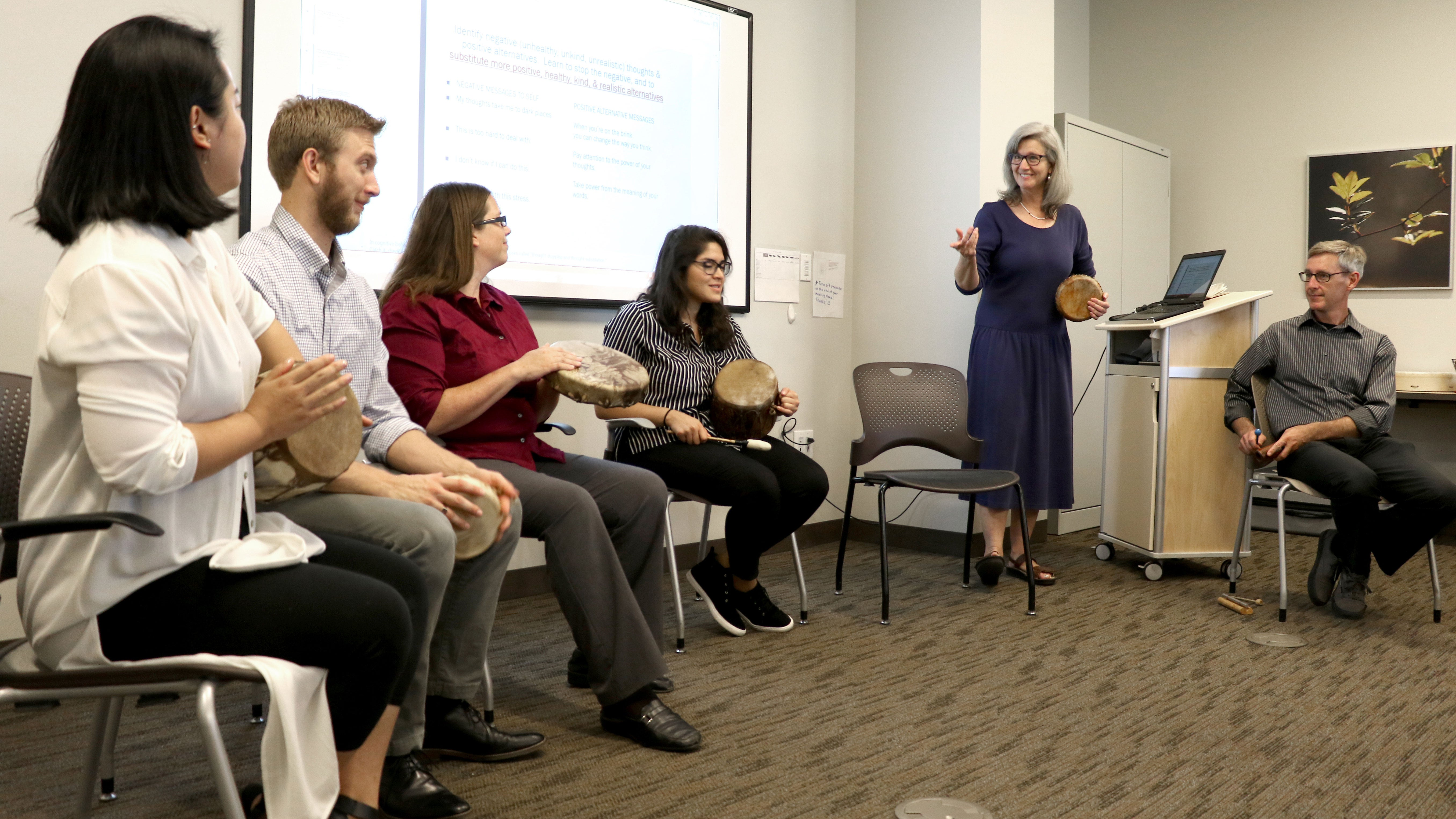 Participants in a drum workshop at a cancer center