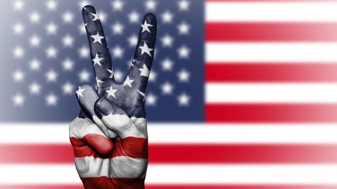 american flag in background, hand making peace sign in foreground