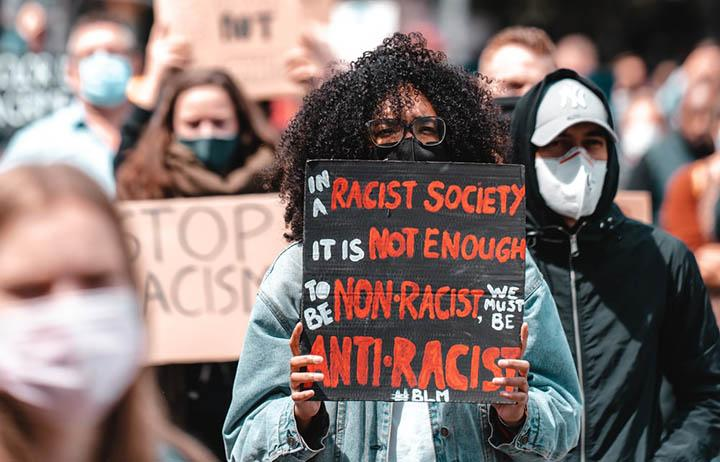 Protest marcher carrying sign: In a racist society it is not enough to be non-racist. We must be anti-racist.